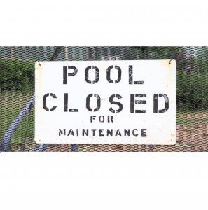 Pool closed for maintenance sign hangs on a fence.