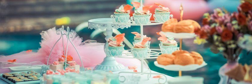 Colourful cupcakes and other finger foods are displayed on a table next to a backyard swimming pool for a party.